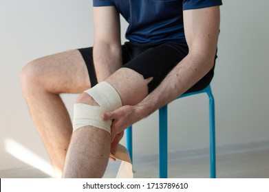 Sporty young man bandaging his knee. Pain in knees. Knee sprain after train sitting on the chair.