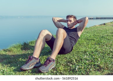 Sporty young man doing sit-ups abs crunches in nature.