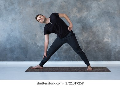 Sporty young man practicing yoga, doing stretching exercise, extended triangle pose, utthita trikonasana asana for flexible spine and relieving stress at studio