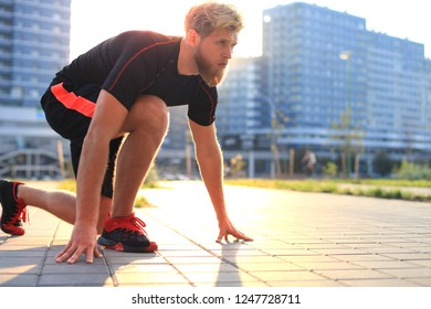 Sporty young man in start position outdoor at sunset or sunrise