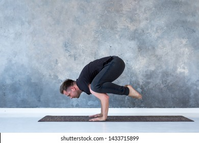 Sporty young man working out, doing handstand yoga asana, Crow Pose or Bakasana. Studio shot