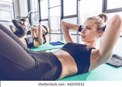 Sporty young people lying on yoga mats and exercising at the gym
