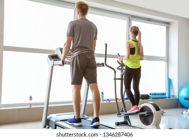 Sporty young people training on machines in gym