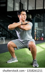 Sporty young Vietnamese man smiling when doing squats in gym