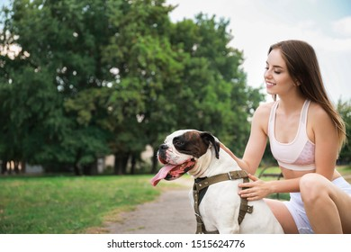 Sporty young woman with cute dog in park