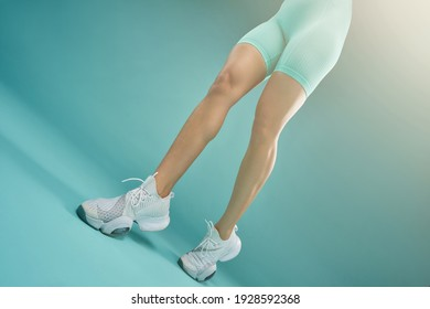 Sporty young woman demonstrating her slender legs
