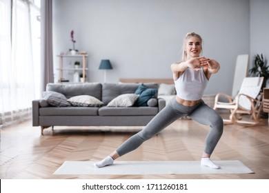 Sportliche junge Frau, die allein im Wohnzimmer Sport treibt.Training zu Hause.