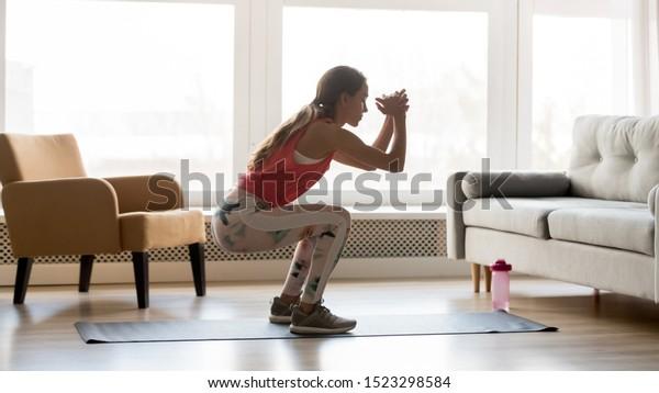 リビングルームで一人でスクワット朝の運動をするスポーツ好きの若い女性、スポーツウェアを着てしゃがむ真剣な体型の女の子、健康的な体のライフスタイルのコンセプト、側面から見て、家で練習する