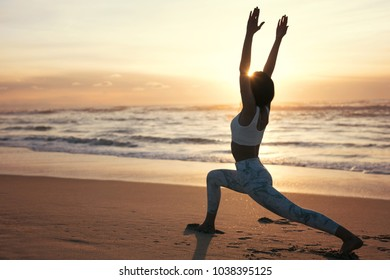 Sporty young woman doing yoga practice at the beach - concept of healthy life and natural balance between body and mental development