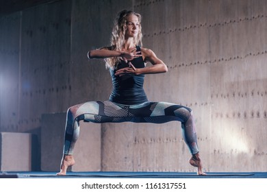 Sporty young woman doing yoga practice. Beautiful happy young girl gymnastics working out in the gym. Healthy lifestyle in fitness club. Stretching.