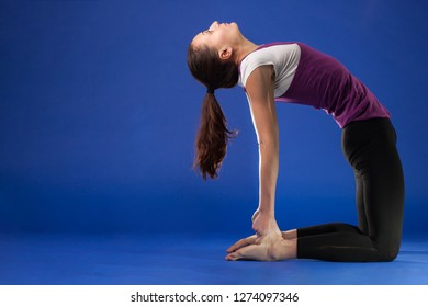 Sporty young woman doing yoga practice isolated on blue background. Concept of healthy life
