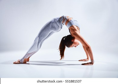 Sporty young woman doing yoga practice isolated on white background - concept of healthy life and natural balance between body and mental development