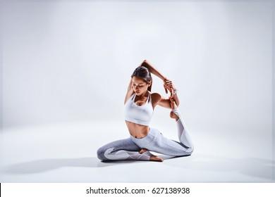 Sportliche junge Frau, die Yoga-Übungen einzeln auf weißem Hintergrund - Konzept des gesunden Lebens und des natürlichen Gleichgewichts zwischen Körper und mentaler Entwicklung