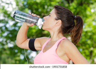 sporty young woman drinking water outdoors