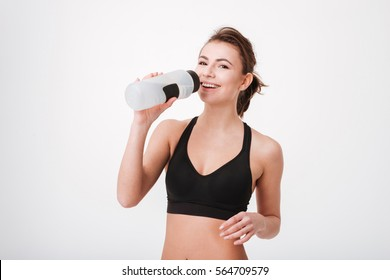 Sporty young woman drinking water after workout isolated on a white background