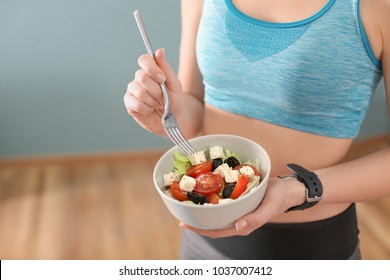 Sporty young woman eating salad after fitness training at home