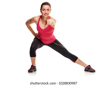 Sporty young woman exercising on white background and pointing on camera