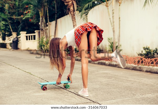 Sporty young woman with fit ass in a sexy red tartan mini skirt takes blue penny skateboard shortboard which stands on the tropical street. Outdoor lifestyle picture on a sunny summer day.