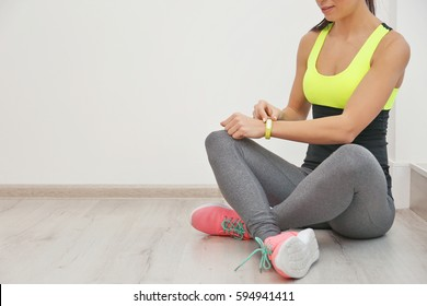 Sporty young woman with fitness tracker sitting on floor in gym
