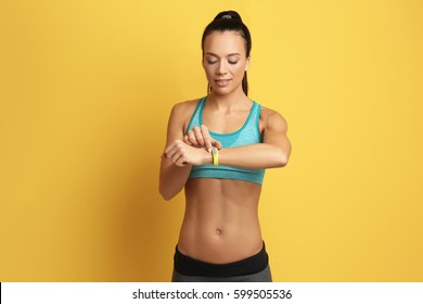 Sporty young woman with fitness tracker on color  background