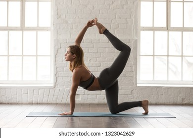 Sporty young woman in grey sportswear, bra and leggings practicing yoga, doing tiger exercise, standing in Bird dog pose, beautiful girl working out at home or in yoga studio with white walls