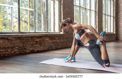 Sporty young woman hatha yoga fitness instructor warmup bend knee stretch leg hip do crescent lunge exercise twisted monkey Anjaneyasana pose gym studio workout health lifestyle concept copy space.