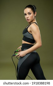Sporty young woman with jump rope posing in studio