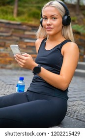 Sporty Young Woman Listening Music With Headphones And Smartphone