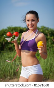 Sporty young woman with measuring tape and vegetables. Outdoors. Concept of healthy lifestyle.