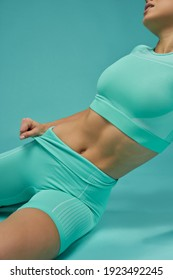 Sporty young woman with perfect abs posing in studio