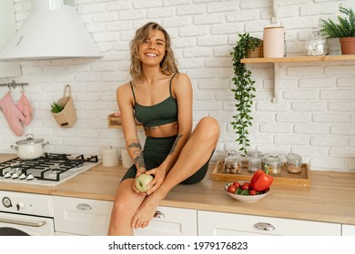 Sporty young woman with perfect body  holdibg apple and posing on light kitchen. Healthy food concept.