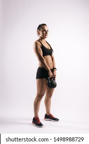 Sporty young woman with perfect muscular body in black sportswear is standing with 12 kg kettlebell and posing on white isolated background.