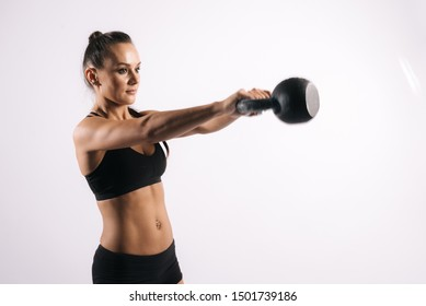 Sporty young woman with perfect muscular body in black sportswearis swinging kettlebell, on white isolated background
