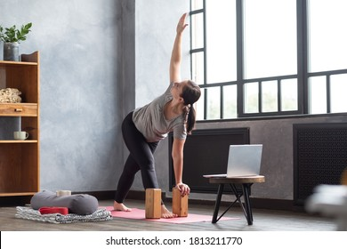 Sporty young woman practicing yoga, doing Revolved Triangle Pose, Parivrrta Trikonasana, working out at home