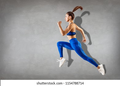 Sporty young woman runing and jumping over gray background.