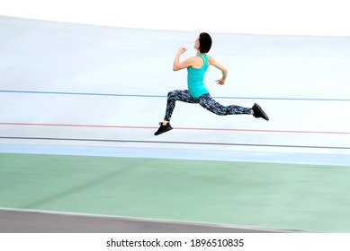 Sporty young woman running by all-season track at the stadium.