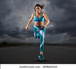 Sporty young woman running on road background
