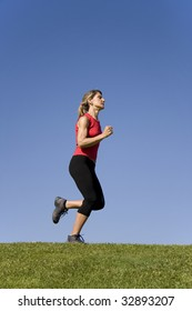 Sporty young woman running on the nature