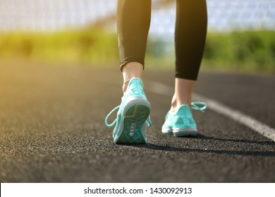 Sporty young woman running at the stadium