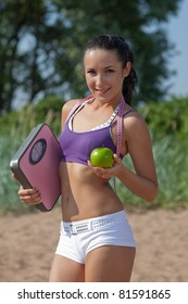 Sporty young woman with scales and green apple. Outdoors. Concept of healthy lifestyle.