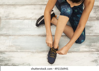 Sporty young woman sitting on wooden background