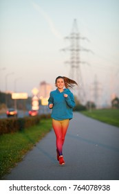 A sporty young woman with a smile on her face dressed in a blue sweatshirt and bright sporting leggings running along the asphalt path lit by the evening sun against the backdrop of the cityscape
