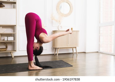 Sporty young woman in sportswear exercising indoors, doing full forward bend, Prasarita padottanasana.