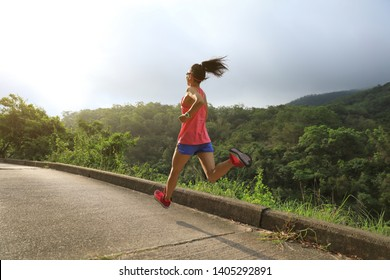 Sporty young woman in sportswear trail running on seaside forest mountain nature path. Fitness girl jogging in Hong Kong