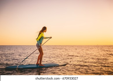 Sporty young woman stand up paddle surfing with beautiful sunset colors
