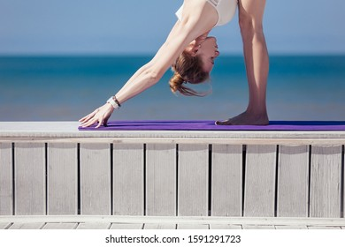 Sporty young woman standing in Downward facing dog exercise, adho mukha svanasana pose. Slim girl practicing yoga outdoor by sea, blue sky, wooden terrace. Calm, relax, healthy lifestyle concept