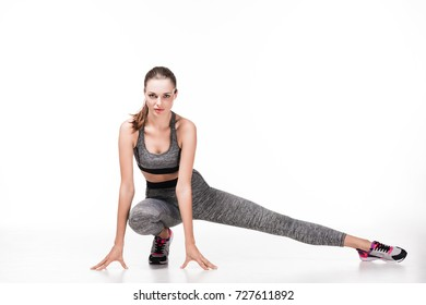 sporty young woman stretching and looking at camera isolated on white