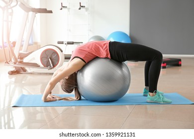 Sporty young woman training with fitball in gym