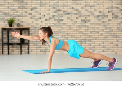 Sporty young woman training at home