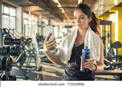 Sporty young woman with water bottle and towel around her neck using phone in gym.